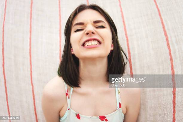 Caucasian woman grinning with bared teeth