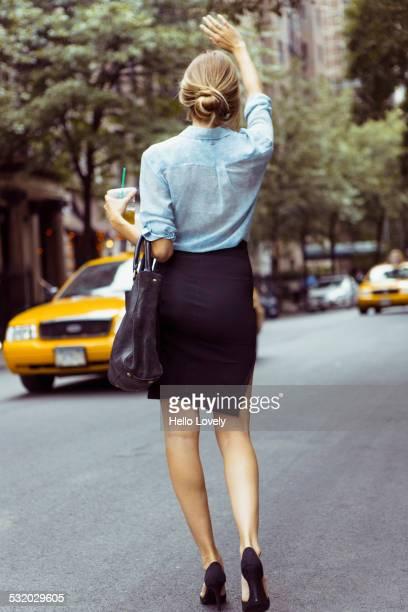 Caucasian woman hailing taxi in urban street