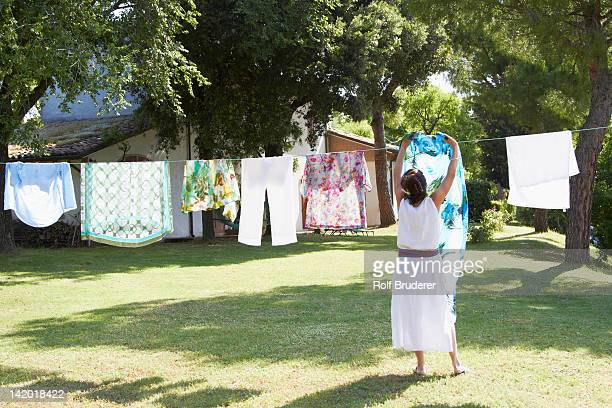 Caucasian woman hanging laundry on clothes line