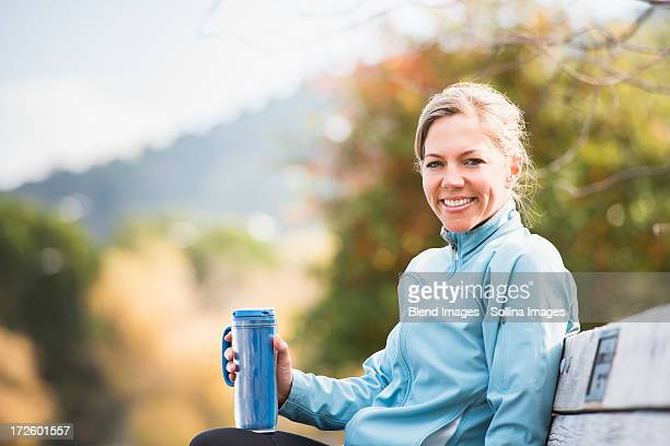Caucasian woman having coffee on park bench