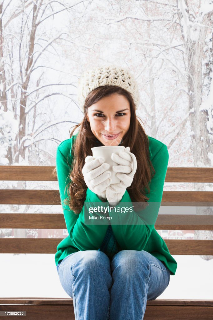 Caucasian woman having cup of coffee in snow