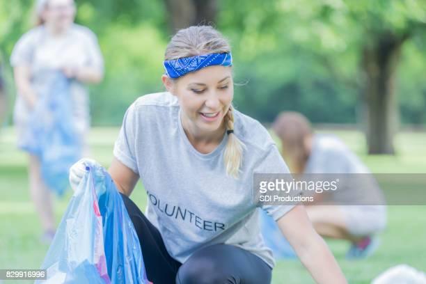 Femme caucasienne aide amis nettoyage communauté