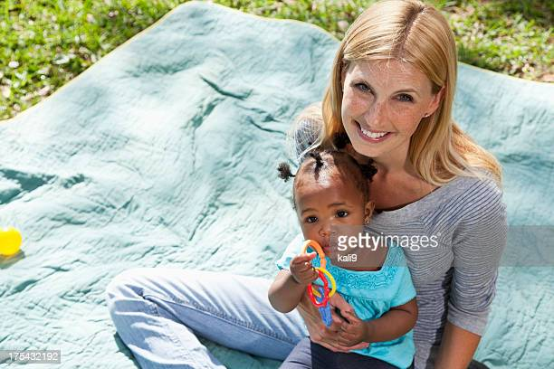 Caucasian woman holding African American baby