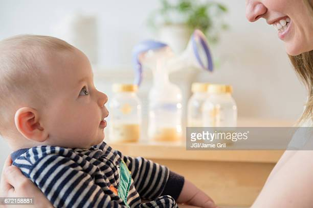Caucasian woman holding baby son near bottles of breast milk