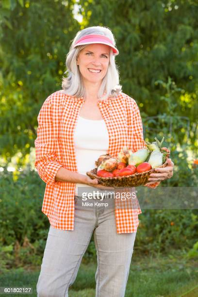 Caucasian woman holding basket of vegetables in garden