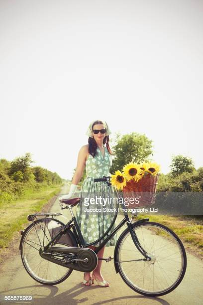 Caucasian woman holding bicycle with basket of flowers