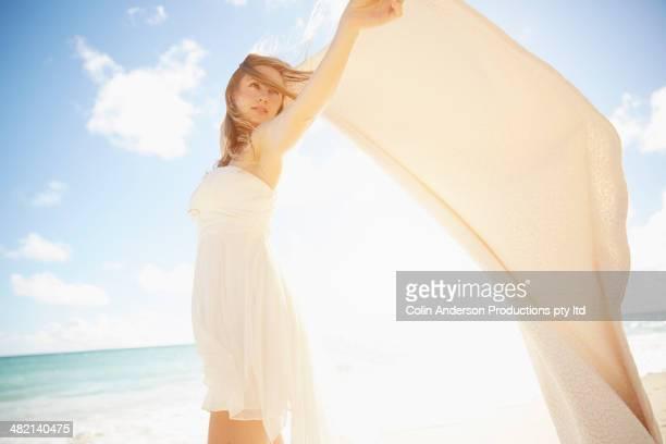 Caucasian woman holding blanket in wind on beach