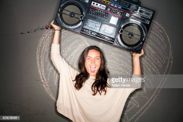 Caucasian woman holding boom box near chalk heart on wall