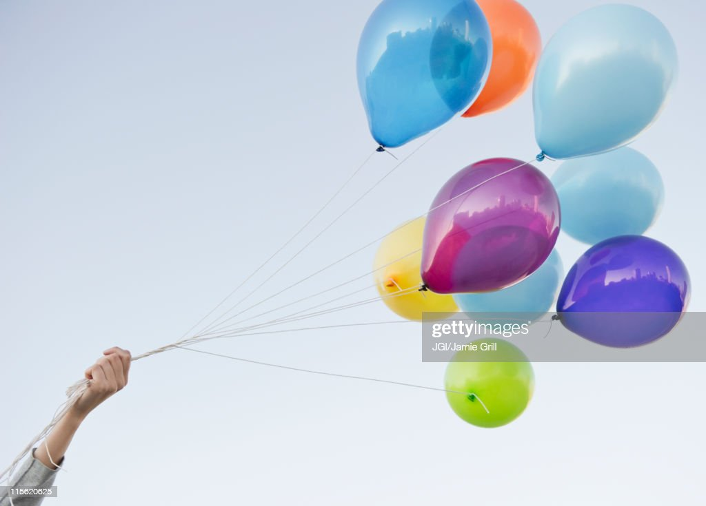 Caucasian woman holding bunch of balloons : Stock Photo