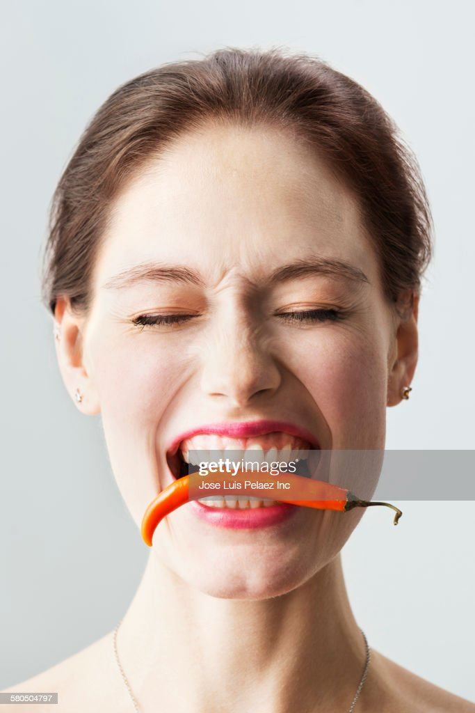 Caucasian woman holding chili pepper between teeth