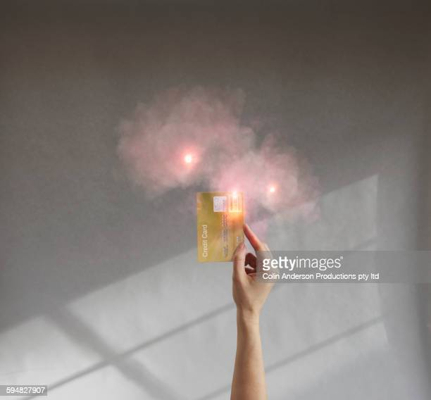 Caucasian woman holding credit card with hazy smoke