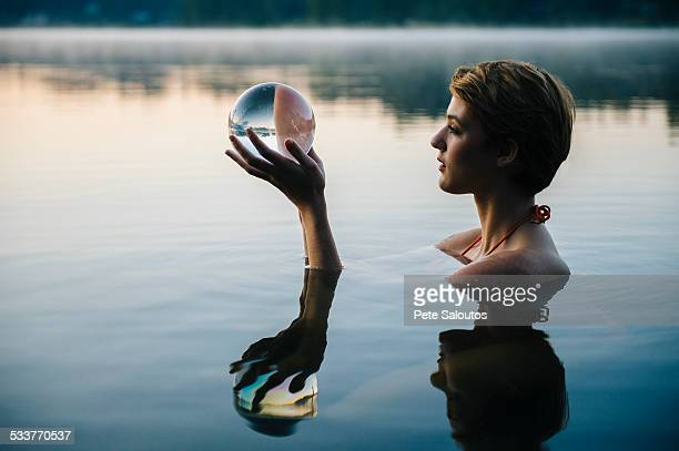 Caucasian woman holding crystal ball in still lake
