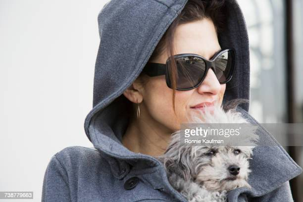 Caucasian woman holding dog in coat