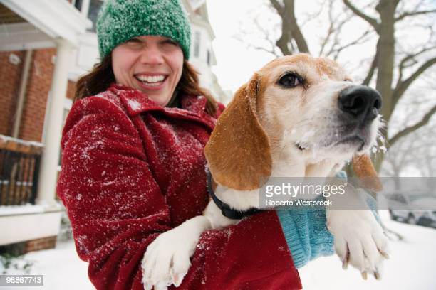 Caucasian woman holding dog in snow
