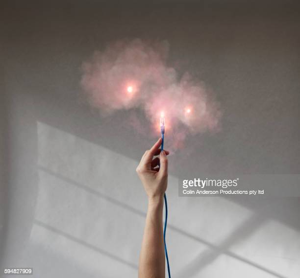 Caucasian woman holding ethernet cord with hazy smoke
