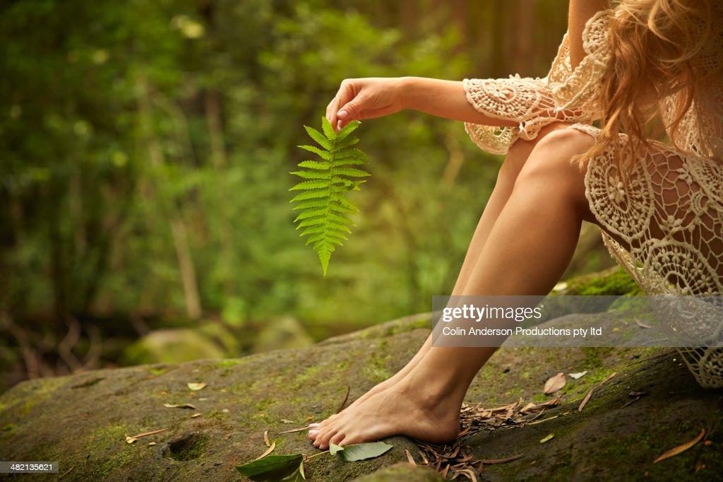 Caucasian woman holding fern leaf in woods
