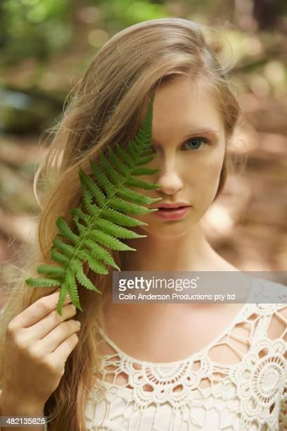 Caucasian woman holding fern leaf outdoors