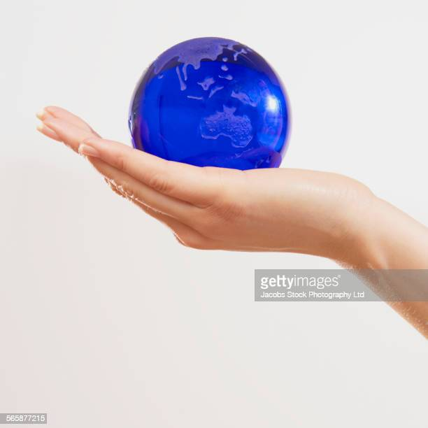 Caucasian woman holding globe in palm