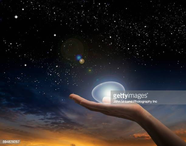Caucasian woman holding glowing egg under sunset sky
