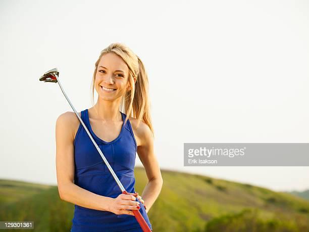 Caucasian woman holding gold club