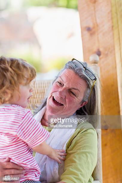 Caucasian woman holding grandson in rocking chair