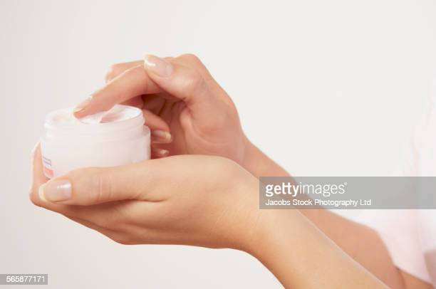 Caucasian woman holding jar of moisturizer