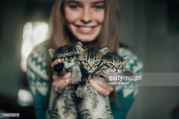 Caucasian woman holding kittens