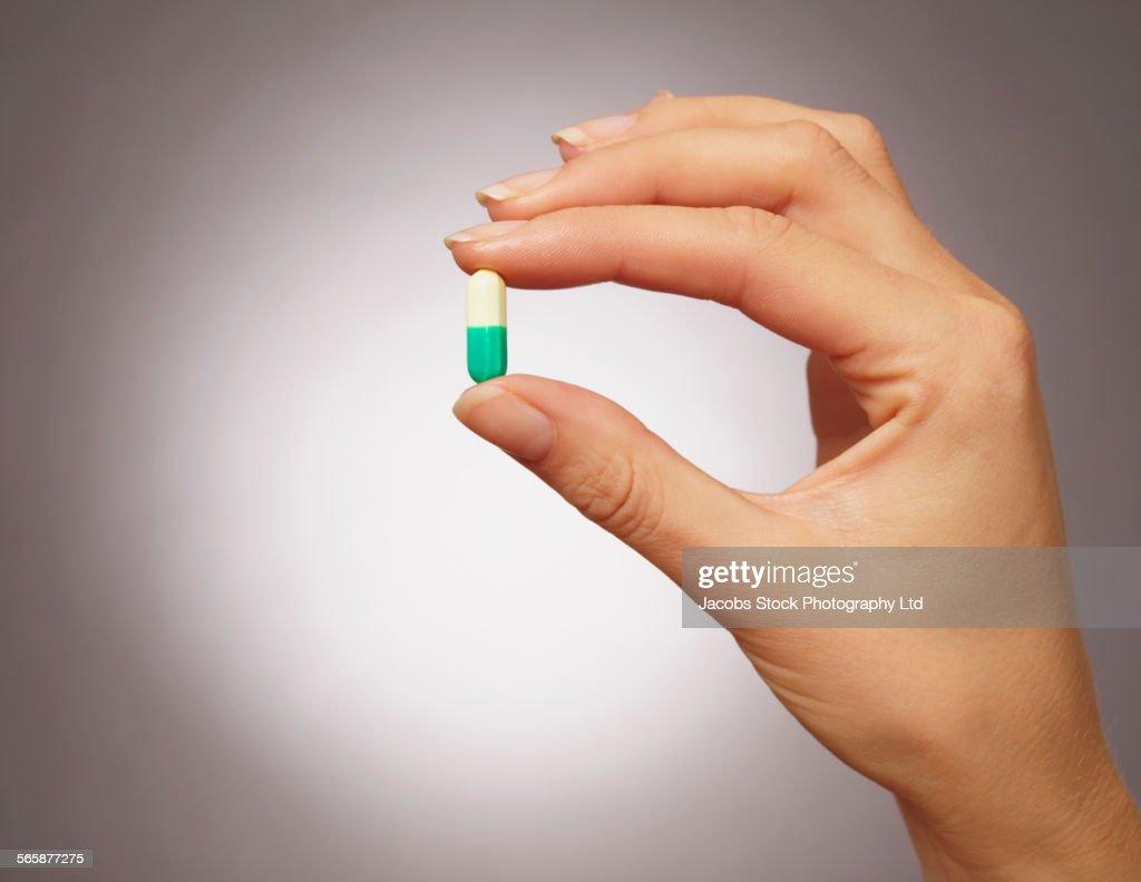 Caucasian woman holding medication pill