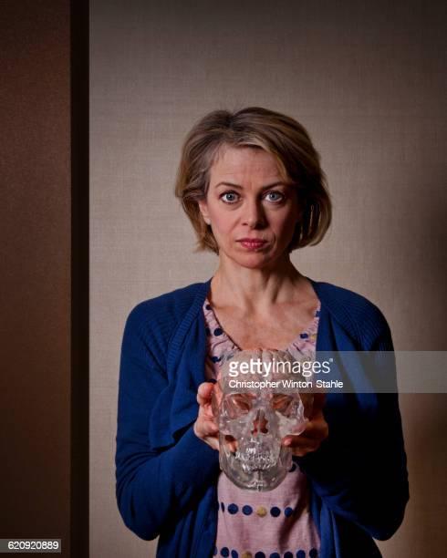 Caucasian woman holding model skull