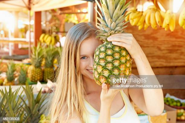 Caucasian woman holding pineapple at produce stand