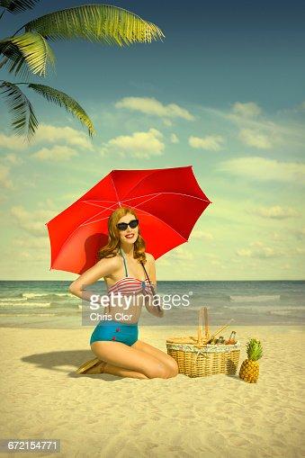 Caucasian woman holding red umbrella at beach