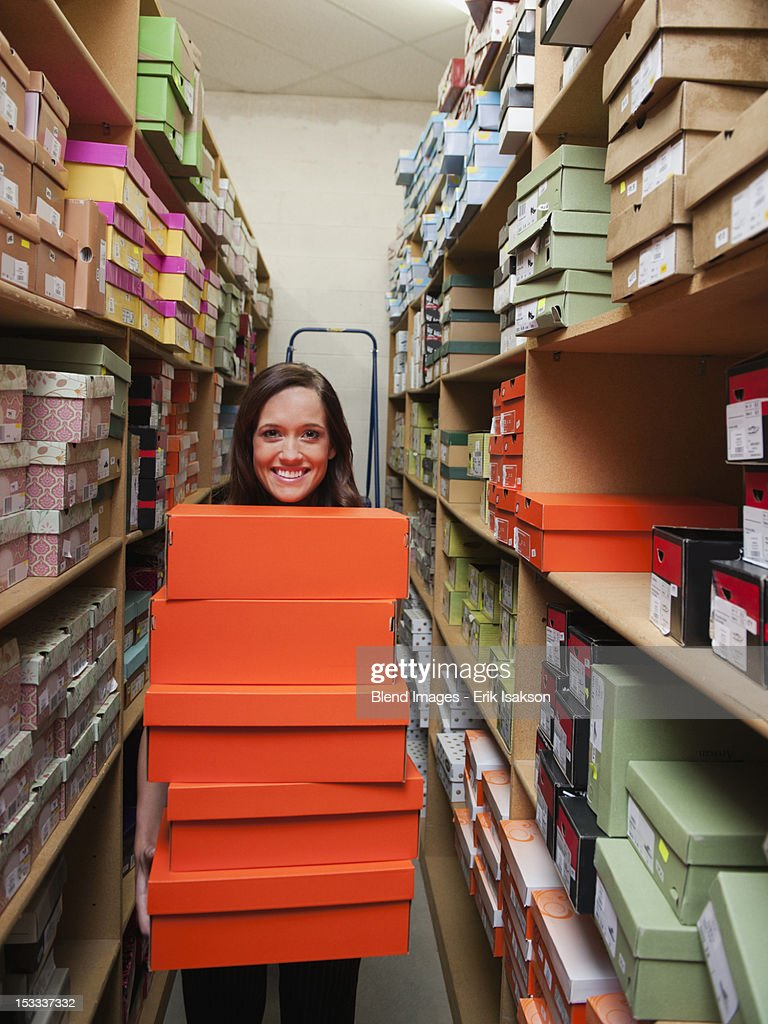 Caucasian woman holding shoes in stockroom