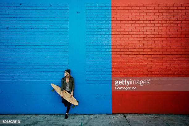 Caucasian woman holding skateboard at painted wall