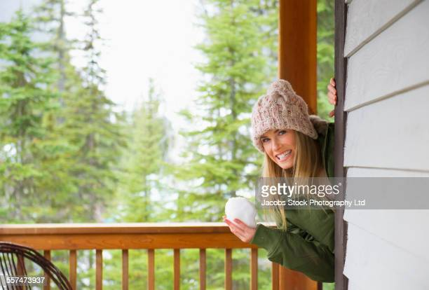 Caucasian woman holding snowball on cabin porch
