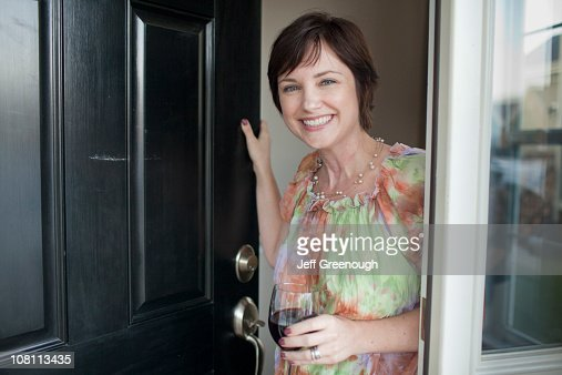 Caucasian woman holding wine glass and opening door