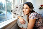 Caucasian woman hugging dog at window