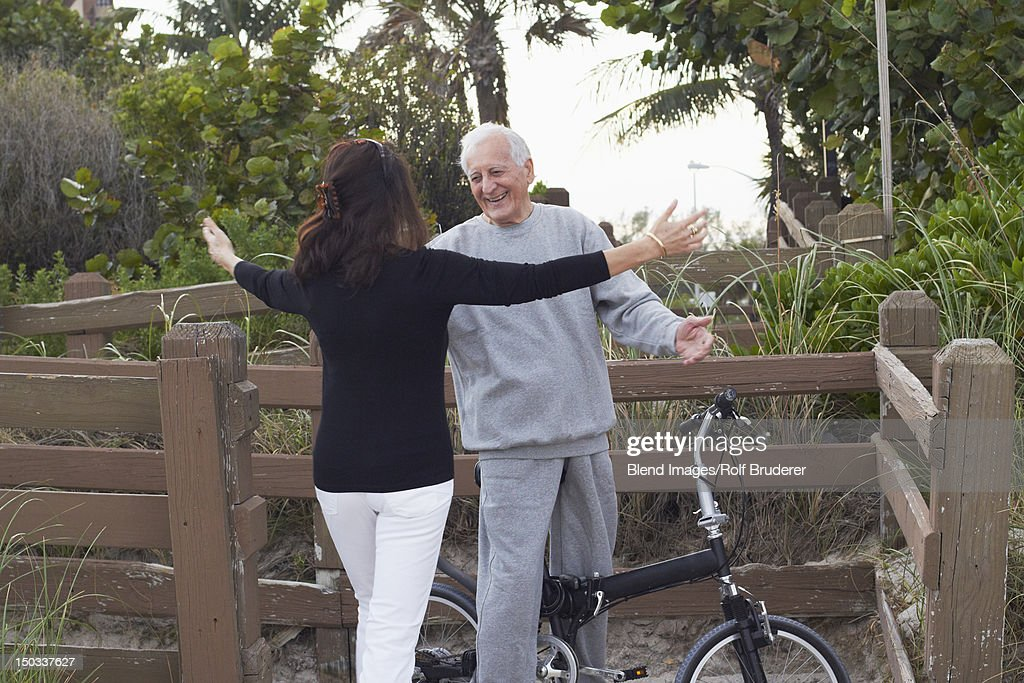 Caucasian woman hugging man on bicycle : Stock Photo