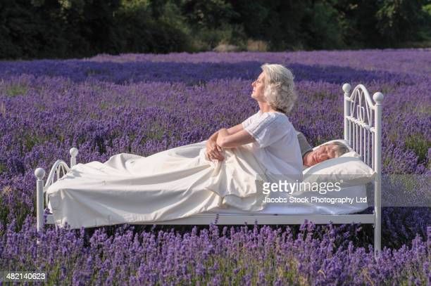 Caucasian woman in bed in lavender field