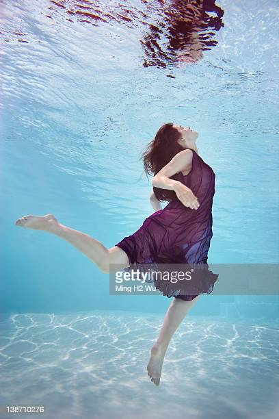 Caucasian woman in dress swimming underwater