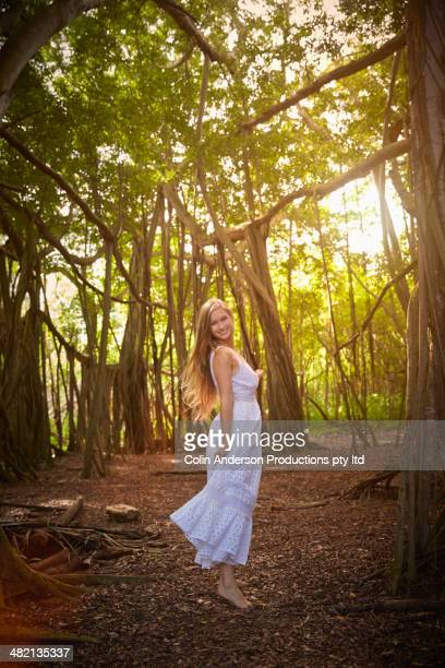 Caucasian woman in dress under banyan trees in forest