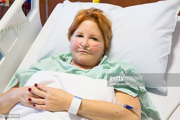 Caucasian woman in hospital bed with oxygen tube