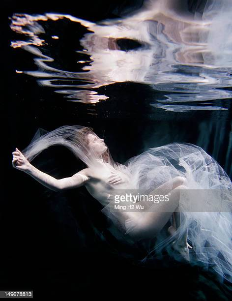 Caucasian woman in scarf swimming under water
