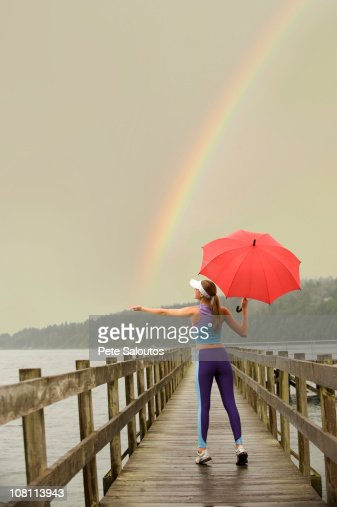 Caucasian woman in sportswear with red umbrella on pier catching rainbow : Stock Photo
