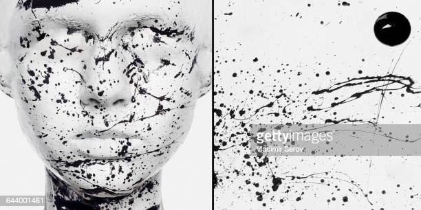 Caucasian woman in white makeup splashed with black paint
