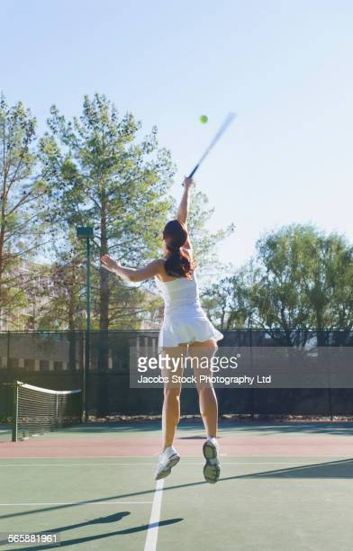 Caucasian woman jumping and serving tennis ball