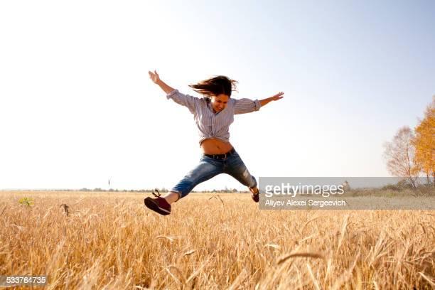 Caucasian woman jumping for joy in rural field