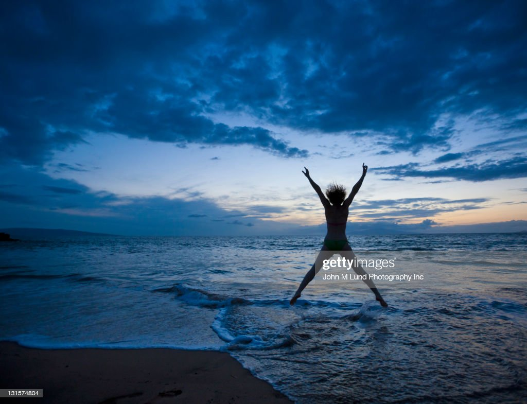 Caucasian woman jumping on beach at sunrise