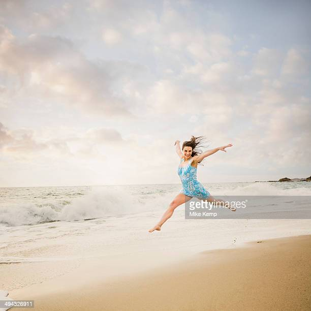 Caucasian woman jumping on beach