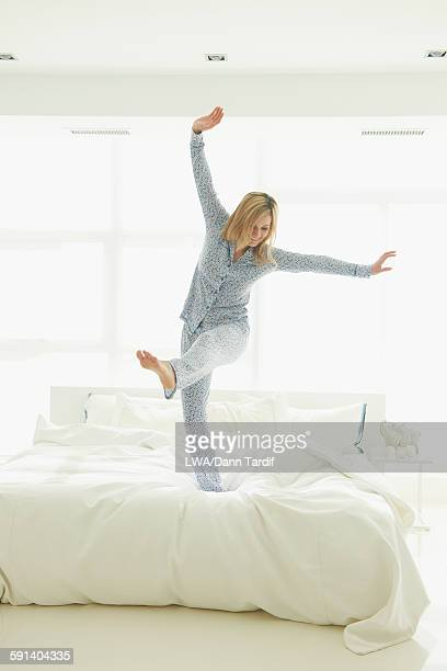 Caucasian woman jumping on bed