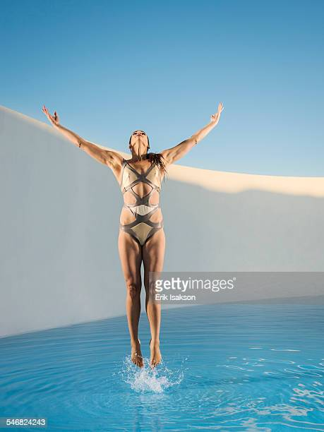 Caucasian woman jumping on swimming pool
